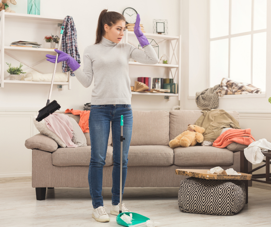 A woman with a broom in a messy den. She needs our Cleaning checklist