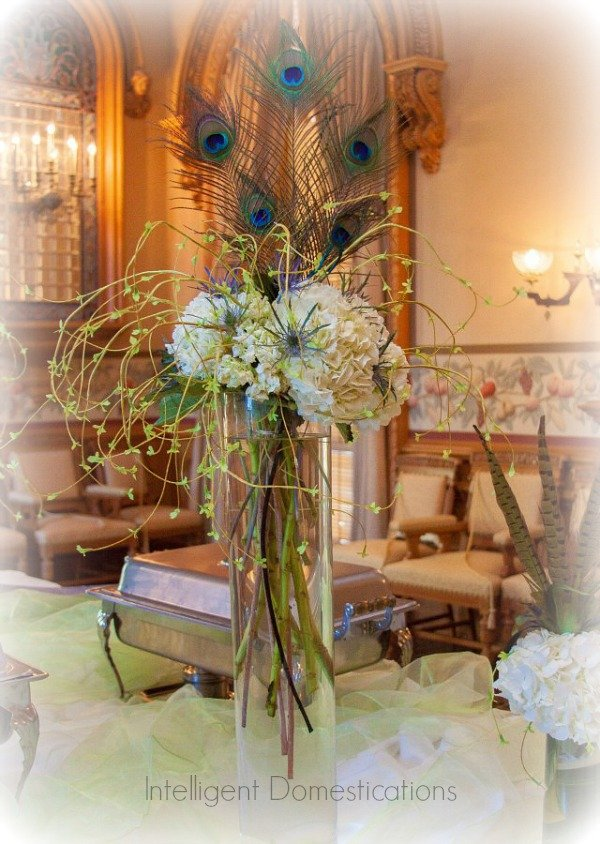 Peacock feathers tucked into floral arrangements. Peacock Theme Wedding Ideas. Tall vases with Peacock feathers and flowers. Peacock theme wedding ideas. #peacockthemewedding