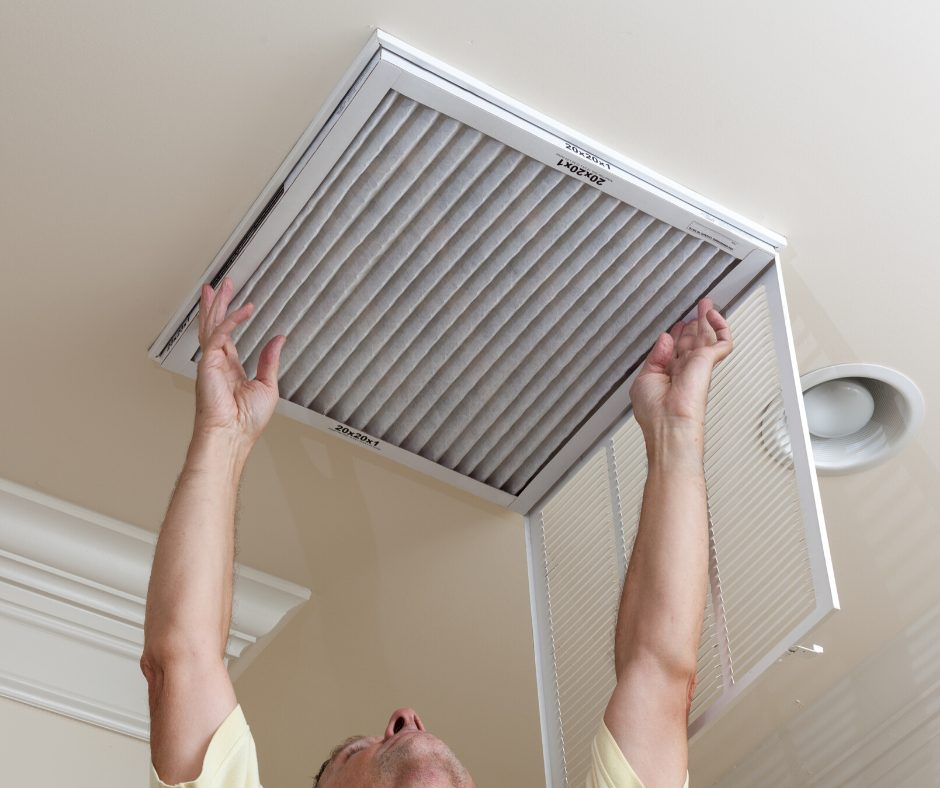 A man changing an air filter for a central unit