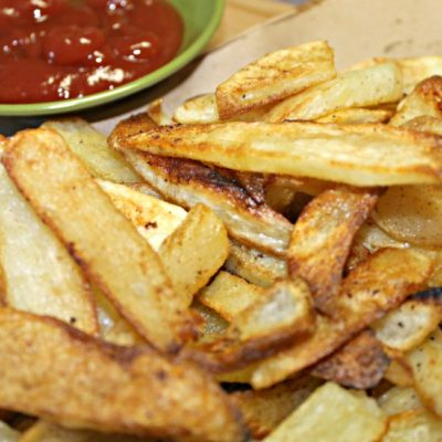 baked french fries on a plate with ketchup