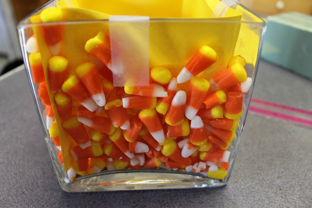 Place the candy corn between the glass and the cardstock. How To Make A Scarecrow Centerpiece. This fun centerpiece or tabletop Scarecrow is made completely with dollar store supplies. He's popping up from the leaves and keeping the candy corn safe. #diy #diyfall #falldecor #scarecrow #candycorn #dollarstore #dollarstoredecor