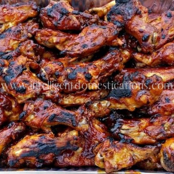 BBQ Chicken Wings with a little char on them piled into a serving pan