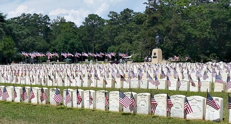 Volunteers place America flags at each and every headstone at Andersonville, Ga. jpg