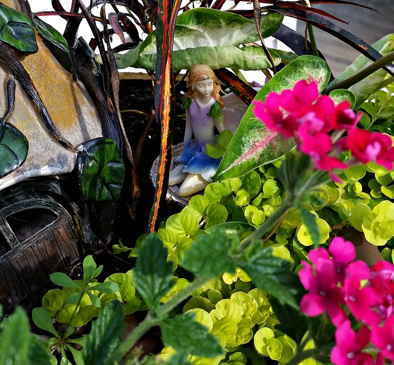 Our Fairy Garden Fairy Princess sitting on a tree stump next to her cottage. My Fairy Garden Tour 2016. Fairy Garden Ideas. Flowers to use in a flower garden. #fairygarden #gnomes #fairygardenideas