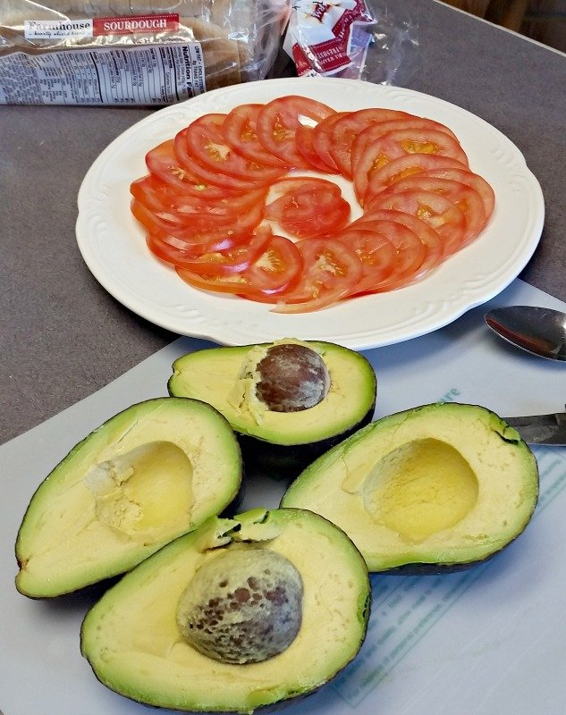 Sliced tomatoes on a white place. Sliced avocados on a cutting board. A loaf of bread nearby