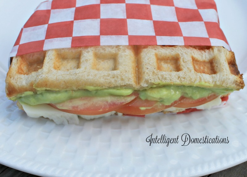 A grilled tomato, avocado and mozzarella sandwich wrapped in a red and white paper on a white plate