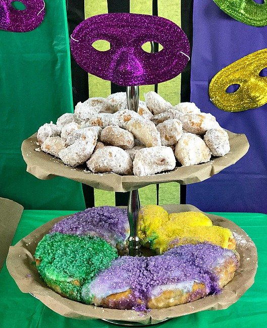 Our Two Tier tray on the Mardi Gras party table displays Biscuit Bignets and a King Cake. Colorful masks create the decor for this celebration. The recipe for the Biscuit biegnets and the King cake are available along with all of our Mardi Gras party ideas. #mardigrasparty #intellid#mardigras