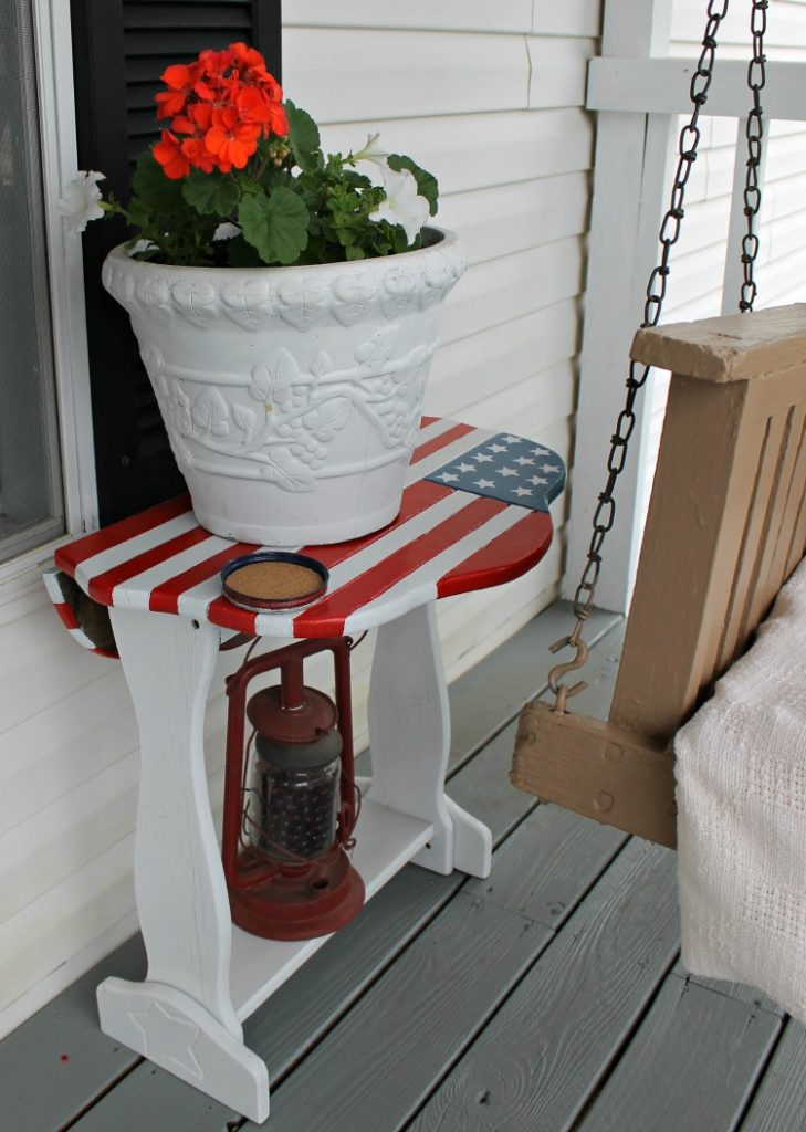 American Flag porch table with white flower pot full of red geraniums and white petunias