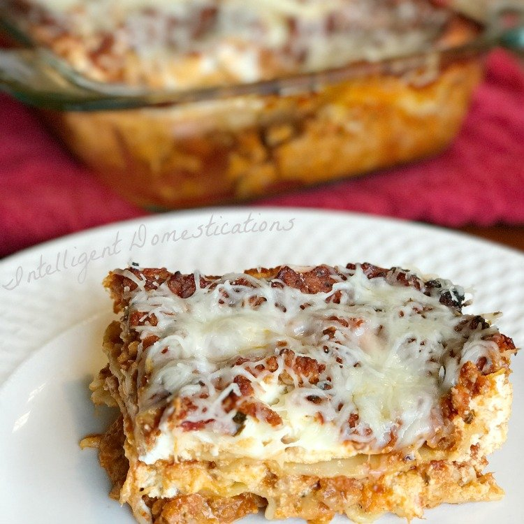 lasagna on a plate in front of a casserole dish with lasagna