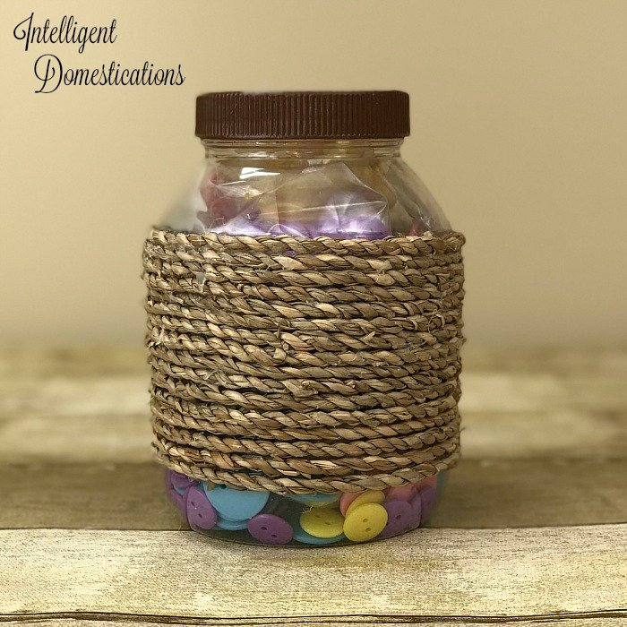 Hot glue rope onto the side of a repurposed mayonnaise jar to create a pretty storage container. Repurpose mayonnaise jars into pretty craft room supply storage containers. Craft room organization. Repurpose mayonnaise jars. Use pretty craft paper to decorate lids of upcycle mayonnaise jars #craftroomorganization