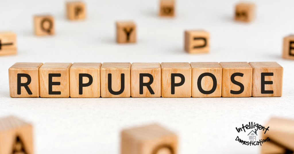 The word 'repurpose' spelled out in scrabble tiles on a table strewn with scrabble tiles on a white background