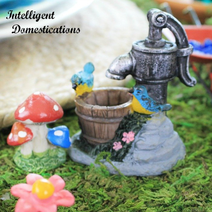 Our Fairy Garden Tablescape is full of whimsy and fun. Gnomes, red polka dot mushrooms, flowers and miniature fairy garden accessories make up a summer Fairy Garden Tablescape for two. Summer Fairy Garden Table. Woodland Gnomes Tablescape. #fairygarden #woodlandtablescape #fairygardentablescape #whimsicaltablescape
