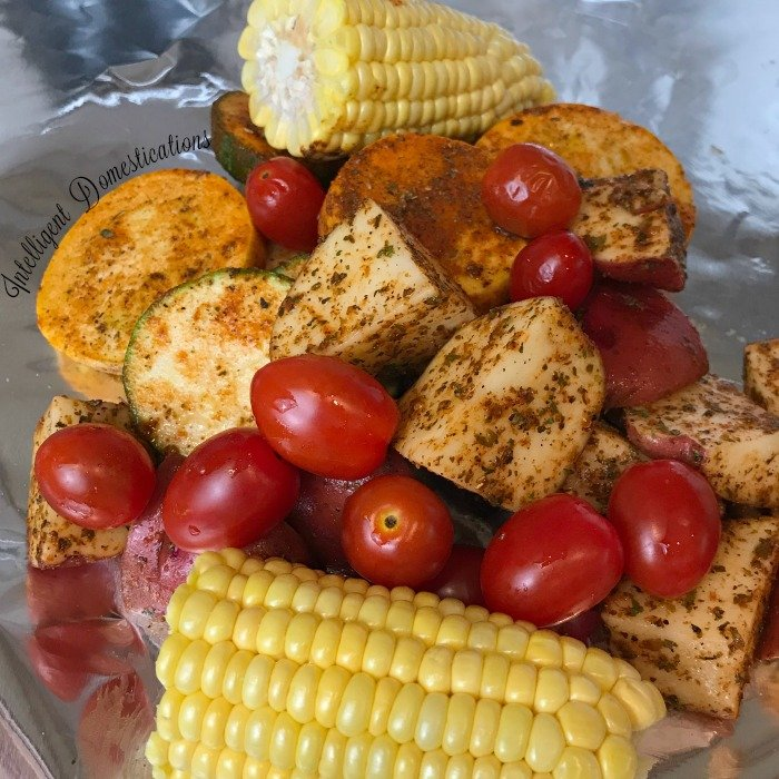 Foil pack dinner recipe. Zucchini, squash, cherry tomatoes, fresh corn and drumsticks make this foil pack dinner delightful and delicious. #foilpackdinner #hobodinner #foilpacketmeal