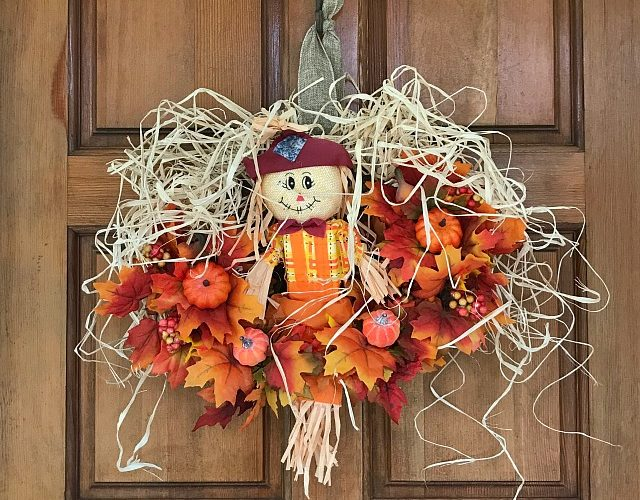 How To Make A Scarecrow Wreath using Dollar store supplies. Fall Wreath tutorial using faux fall leaves and a Scarecrow for the center. #fallwreath #diyfallwreath #scarecrowwreath #diydecor #craft #fallcraft #fall