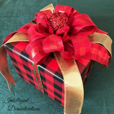 A gift wrapped in red and black plaid paper with a red bow on top and gold ribbon draped down the sides