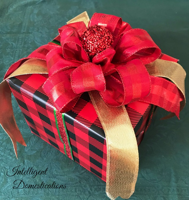 A gift wrapped in red and black plaid paper with a big red bow with gold tails