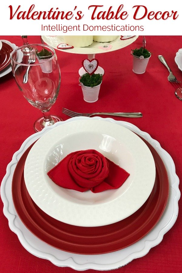 Simple Valentine's Table Decor Ideas using what we have. Rose folded napkins along with a layered red and white table setting create this pretty Valentines Tablescape. #Valentinestabledecor #valentines