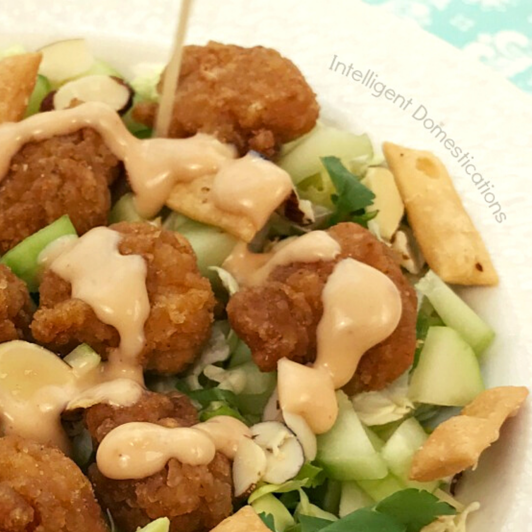 Salad in a white bowl with chicken tenders and dressing being poured over it