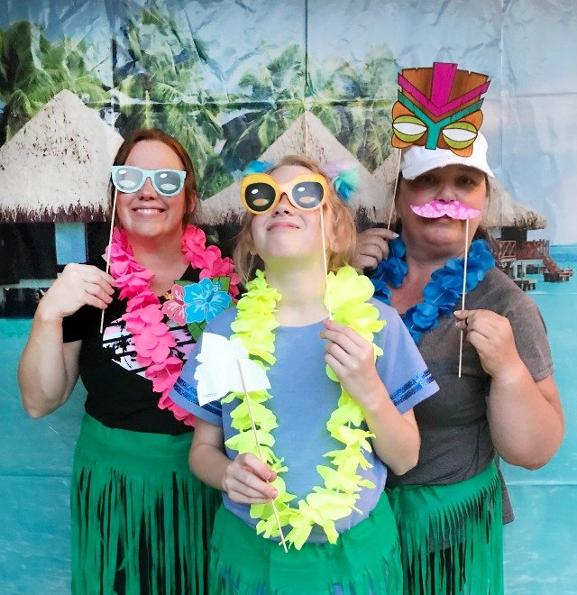 Three ladies posing for a photo dressed in Luau party leis and grass skirts holding photo stick props