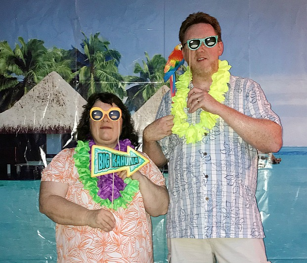 A couple posing in front of an ocean backdrop wearing Luau party attire with leis around their neck and holding photo stick props
