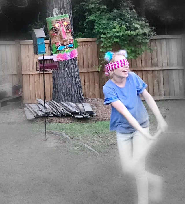 A girl wearing a blindfold swatting at a Pinata