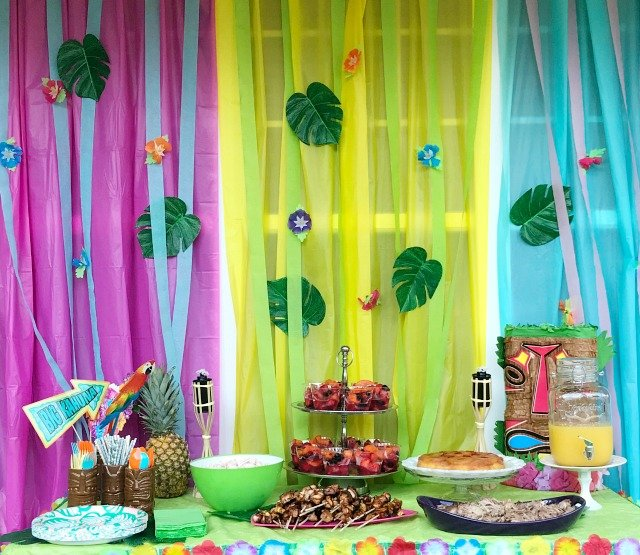 Luau party table covered with food and a colorful backdrop