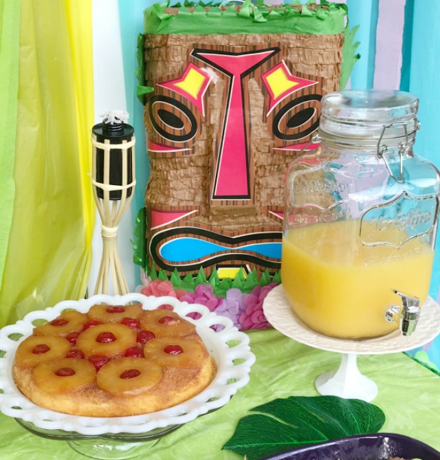 Luau party food table with Pineapple upside down cake and orange punch