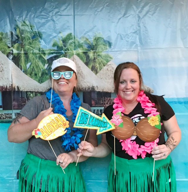 Two ladies posing in front of a Luau party backdrop dressed in grass skirts and wearing leis while holding photo stick props
