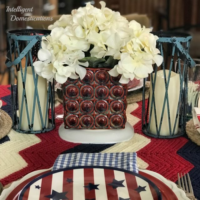 Our Red White and Blue Tablescape Decor this year incorporates a family heirloom afghan as the tablecloth. The place setting is a layered look with a Patriotic 4th of July dessert plate on top. See the centerpiece and all of the little touches of this Patriotic Table Decor #4thofJuly #RedWhiteandBlue #Tabledecor