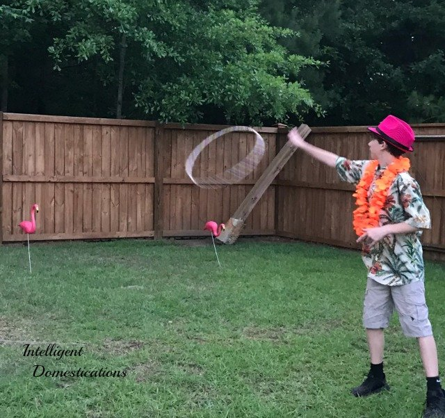 A boy playing a Pink Flamingo Ring Toss game outside