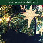 Wood silhouette nativity ornament painted black with a silver star hanging on a Christmas tree