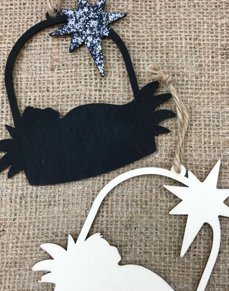 Two thin balsam wood pieces cut into a Nativity silhouette design for a Christmas Ornament. One is painted black with a shiny silver star. The other is not painted.