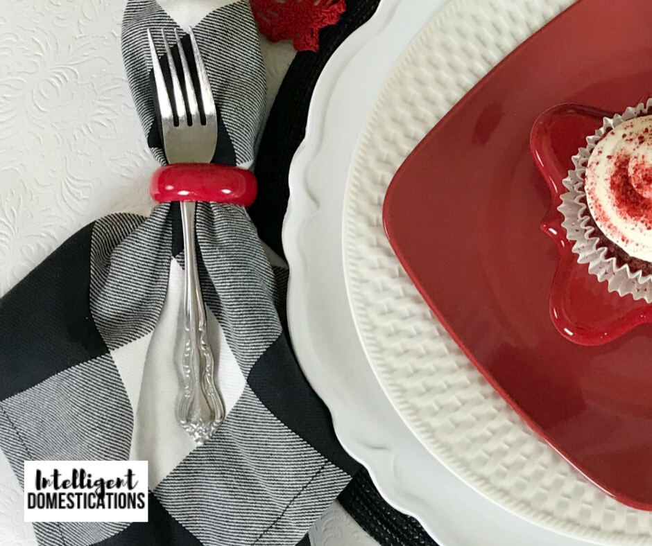 Black and White buffalo plaid napkins create pop with a red and white plate stack on this Valentines Tablescape
