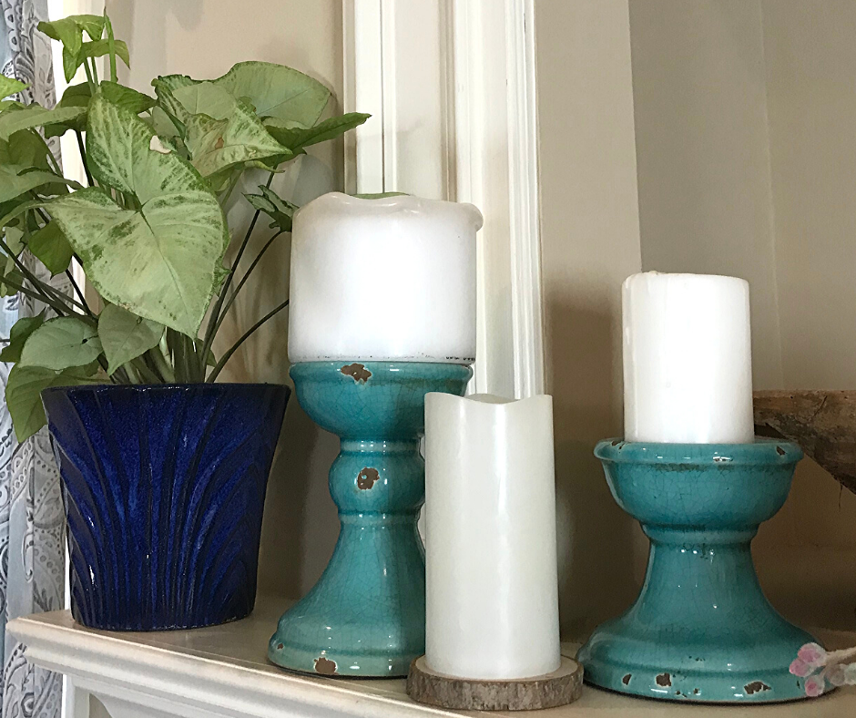 Tips for Decorating a Spring Mantle with plants, candles and greenery. I used what I had on hand including old candle holders which can double as cake plate stands. A live houseplant anchors this little mantle vignette.