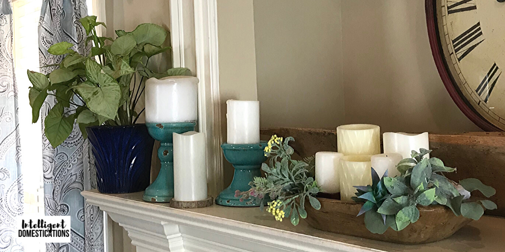 Decorating a large mantle for Spring using mini vignettes. Candles, faux greenery and a live plant decorate this mantle for Spring on a budget.