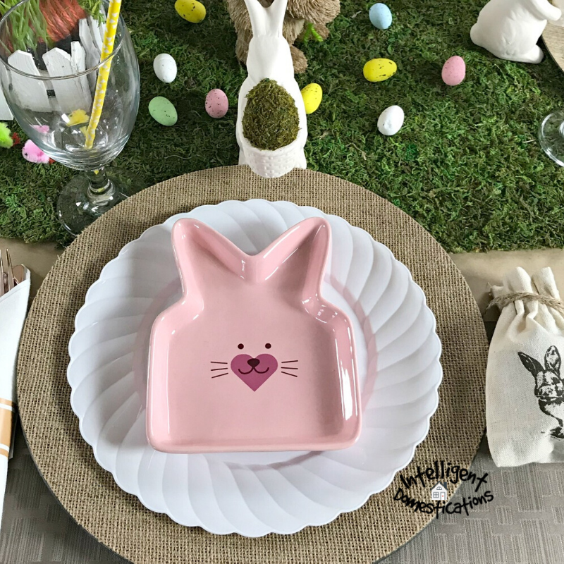 Easter Tablescape place setting. Burlap charger is topped with a white dinner plate and a pink bunny ear shapped salad or dessert plate. #tablescape #Eastertable #Easterdecor