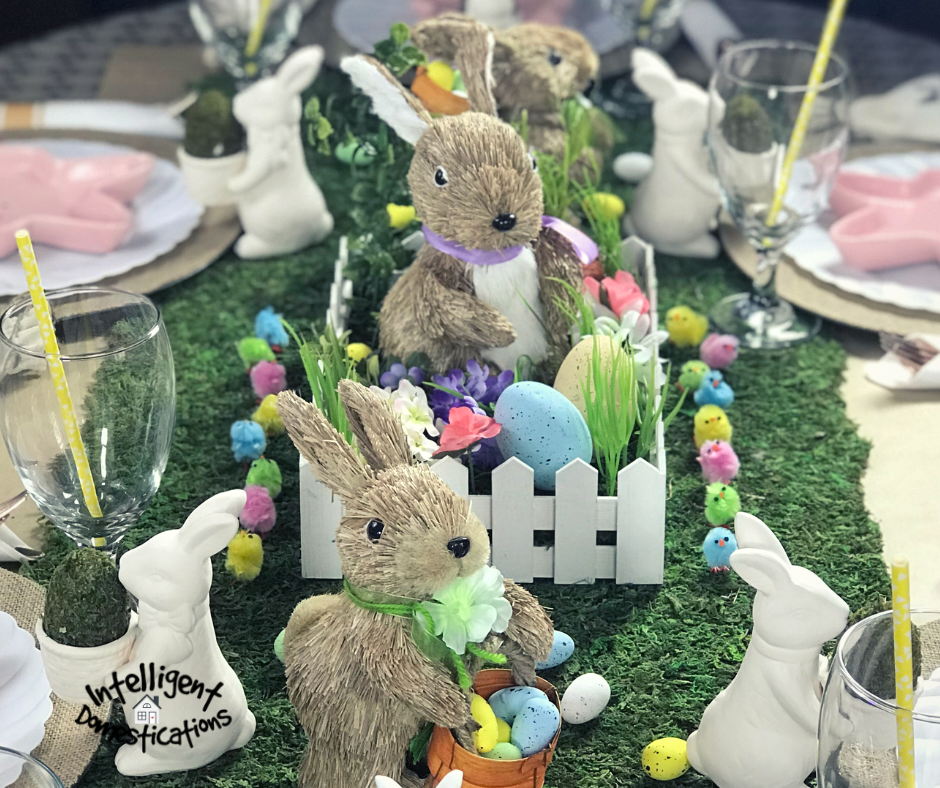 Easter Table Centerpiece. A wood fence holds a Sisal Easter Bunny surrounded by pastel colored Easter eggs. This centerpiece is adorable for Easter Table decor. #easterdecor