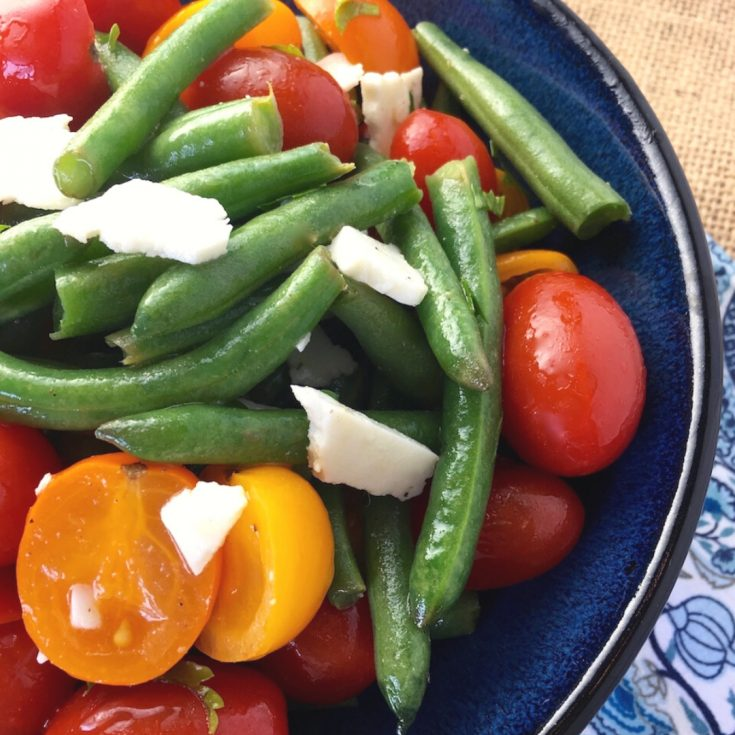 Farm fresh green beans paired with Grape tomatoes and feta make a delicious summer salad. Great side dish for summer BBQ's. Serve it immediately or chill to serve cold. #summersideddish #summersalad #farmfresh #greenbeans #saladrecipe