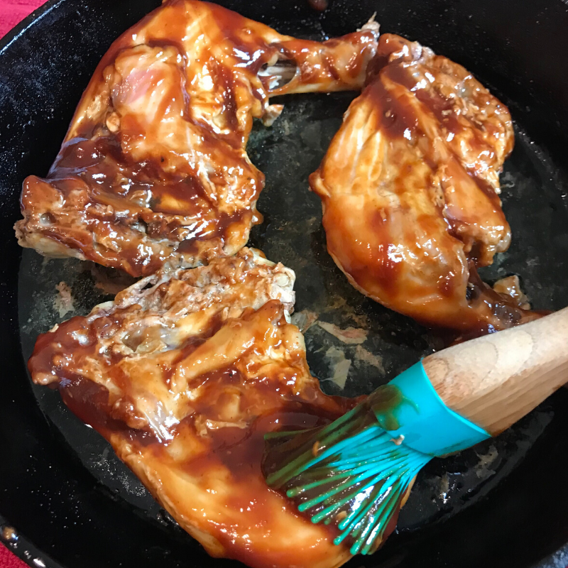 Turn the chicken over and baste with BBQ sauce