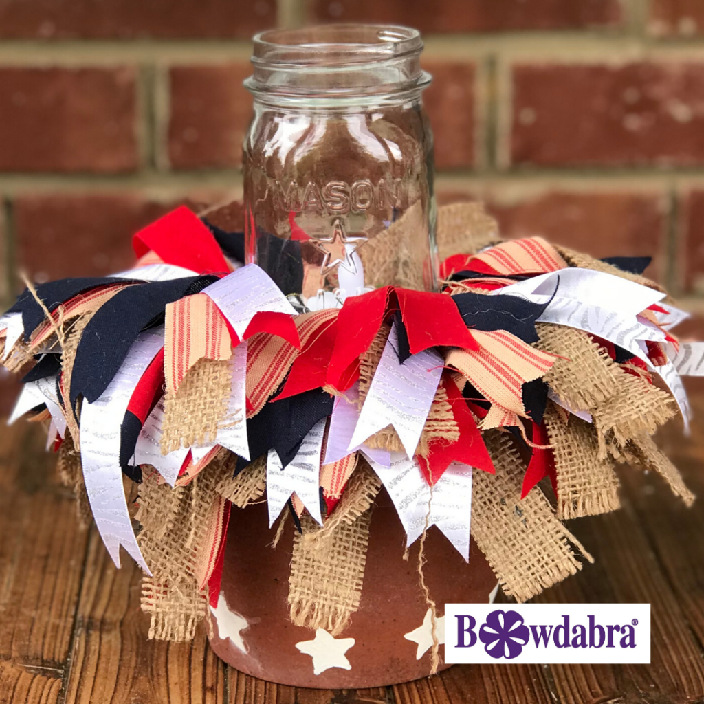 A red white and blue centerpiece which is a terracotta clay pot with white stars on the bottom, ribbons spilling out and a Mason jar candle in the center. Pictured outside on a wood table with a brick wall in the background