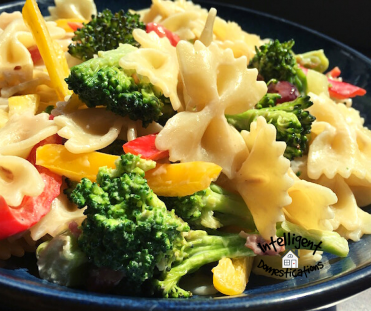Bow Tie Pasta Salad with broccoli and peppers displayed on a dark plate