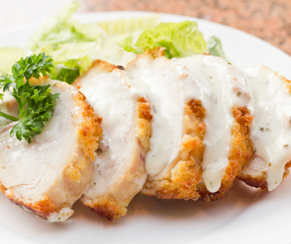 Lightly battered Chicken Cordon Bleu served on a white platter with a creamy sauce poured over
