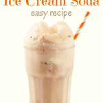 A tall glass filled with Chocolate Ice Cream Soda with an orange and white straw on a white background