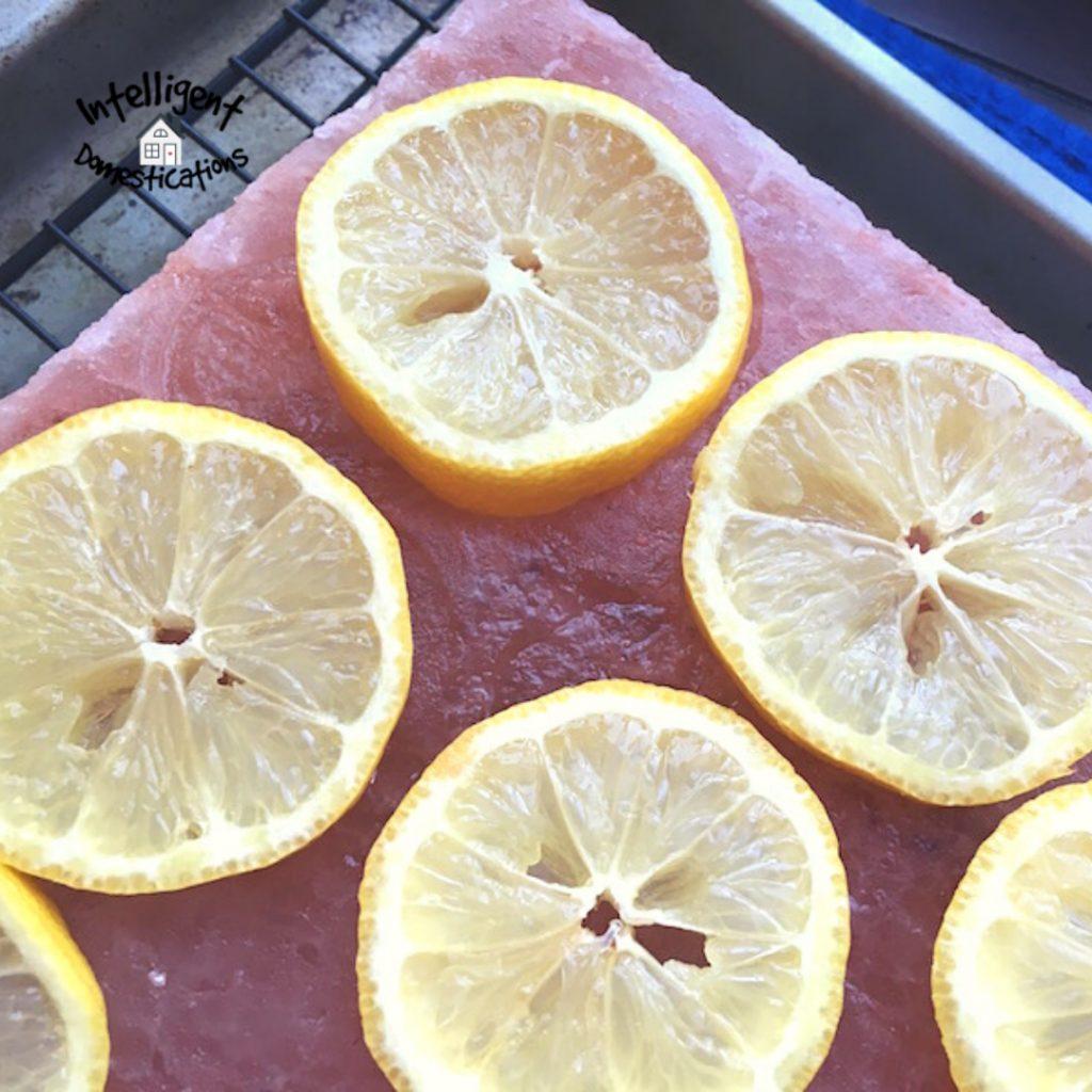 Lemon slices resting on a pink salt block