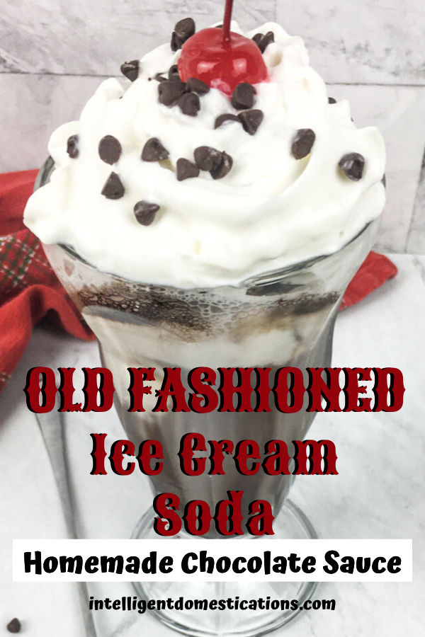 Close up image of an old fashioned chocolate ice cream soda in a tall glass with whipped cream and a cherry on top and chocolate sprinkles on a white background with a red towel on the counter