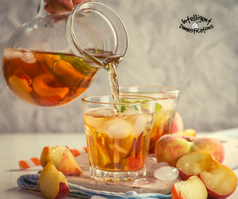 Iced tea being poured from a pitcher into a glass with ice and cut peaches displayed on a table