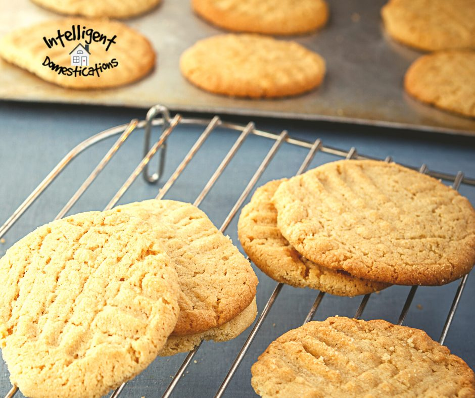 Peanut Butter Cookies fresh from the oven on a cooling rack with more cookies on the baking sheet in the background