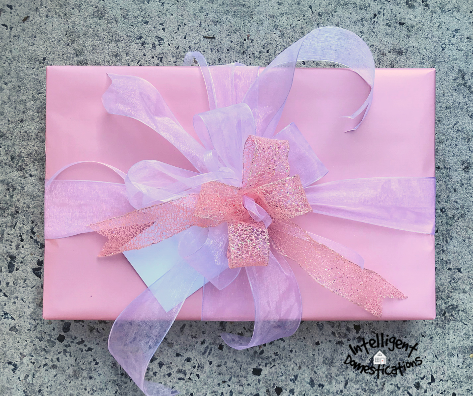 A gift box wrapped in pink paper with pink ribbons and bows on top