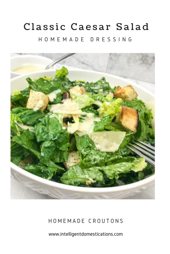 A white bowl of Caesar Salad with a fork on the side of the bowl
