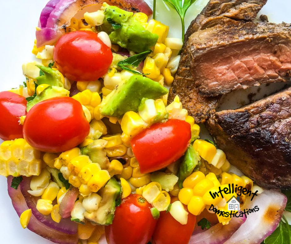 Corn, Tomatoes, Onions and Avocados mixed together in a salad served next to a steak